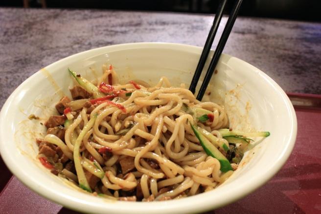 炸酱面 (zha jiang mien) is a dish of noodles, ground pork, soybean sauce, fresh cucumbers, and more.